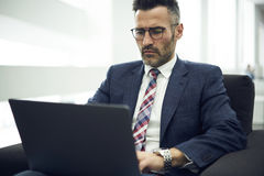 Adult man in a jacket and glasses testers via online chat correcting bugs to improve program usability quality control Royalty Free Stock Images