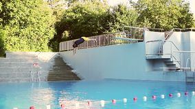 An adult man jumping into the water. Dad and son are swimming in the outdoor pool. Slow motion. 120fps stock footage