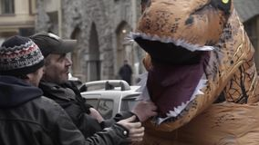 Adult man kisses t rex mascot costume head at city street. Adult caucasian scruffy man kisses t rex mascot costume head at city street. Cold sunny spring or stock video footage