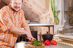Adult man on kitchen cutting greenery Royalty Free Stock Photography