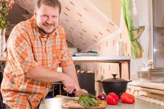 Adult man on kitchen cutting greenery Stock Photos