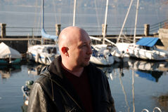 Adult man on the lake. Portrite of adult man (40-45) with boats and yachts on the lake Royalty Free Stock Photography