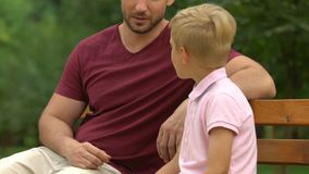Adult man and little boy having serious conversation on bench, role model stock footage