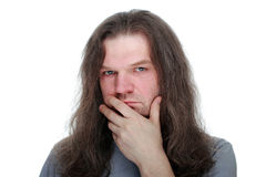 Adult man with long hair looking thoughtfully at the camera. Adult man with hand to mouth and long hair looking thoughtfully at the camera, white isolated Stock Photo