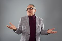 Adult man looking away and making helpless gesture. Calm adult person standing isolated against the grey background and thoughtfully looking into the distance royalty free stock photo