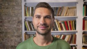 Adult man looking forward, smiling and blinking calmly. Bookshelves on the background