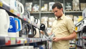 An adult man looks at electric kettles that stand on a rack in a shopping center stock video