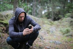 Man in forest lost. Adult man lost while hiking  in the forest and using phone for helping Stock Photography