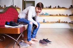 Adult man with a lot of shoes Royalty Free Stock Photography