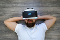 Adult Man lying on his back in virtual glasses on a wooden floor stock images