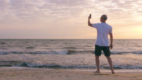 Adult man making selfie andmobile photo morning sunrise on sea beach
