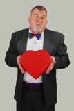 Adult Man Offering Valentine's Day Kiss and Candy. An adult man dressed in formal wear offers a kiss and heart shaped box of chocolates Royalty Free Stock Images