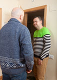 Adult man opening door his neighbor. Adult men meeting another men at door royalty free stock photography