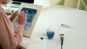 Adult man paint with colored watercolor paints in an home studio. 4k
