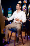 Adult man palyng the slot machine Royalty Free Stock Image