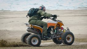 An adult man performs a trick on a sports quad bike riding on a sandy beach, a person professionally manages an extreme stock video footage