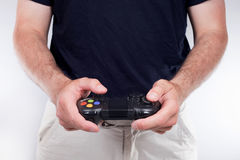Adult man playing videogames. Hands of adult man playing videogames, sitting on white sofa with joystick controller in hairy hands, wearing black t-shirt Royalty Free Stock Images