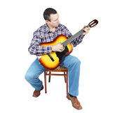 Adult man plays a guitar sitting on an chair Stock Photography
