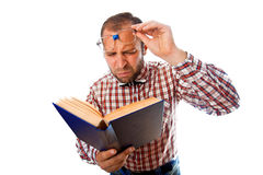 Adult man with poor eyesight try to read a book Stock Images