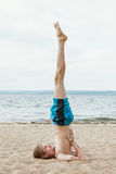 Adult man practices yoga on the beach Royalty Free Stock Images