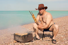 Adult man prepares fried meat. On the lake. Rest. Royalty Free Stock Images