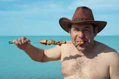 Adult man prepares fried meat. On the lake. Rest. Royalty Free Stock Photography