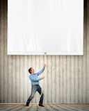 Adult man pulling blank banner Stock Photos