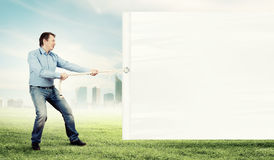 Adult man pulling blank banner Royalty Free Stock Photography