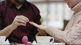 Adult man puts wedding ring on his girlfriend`s finger and kissing her. By table in a cafe stock footage