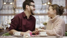 Adult man putting a wedding ring on his girlfriend finger making her a proposal. In a restaurant by table stock video