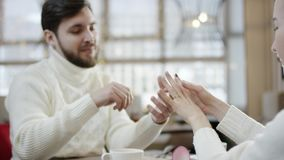 Adult man putting wedding ring on his girlfriend`s finger. Adult bearded man putting wedding ring on his girlfriend`s finger in a cafe by table stock footage