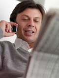 Adult man reading stock exchange listings at home Royalty Free Stock Images