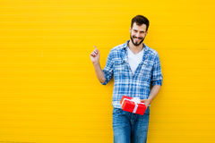 Adult man with red gift. Adult man smiling with beard with red present on yellow background, showing on his right text space Royalty Free Stock Photography
