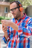 Adult man relaxing with headphones, listening to music. Orange f Stock Images