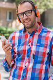 Adult man relaxing with headphones, listening to music. Orange f Stock Photography