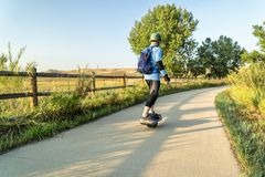 Riding electric skateboard on bike trail Royalty Free Stock Photo