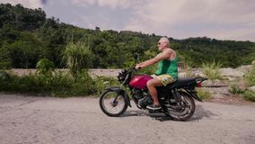 Adult man riding motorcycle on road on nature landscape. Senior man traveling on motorbike driving at road. Motorcycle. Adult man riding motorcycle on road on stock video footage