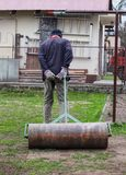 Adult man rolling heavy iron barrel for better condition garden after winter. Human wears working outfit. Manual work in the. Garden. He is trying flatten stock photos