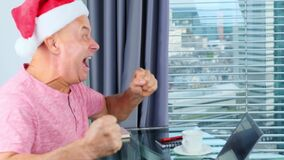 Adult man in santa claus hat sits in front of a laptop, surfs information and reacts emotionally, concept of christmas, new year