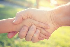 An adult man shakes hands with a child. The concept of salvation. An adult man shakes hands with a child. Dad holds his son& x27;s hand. The concept of salvation Royalty Free Stock Photo