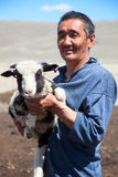 The adult man  shepherd. The adult man the shepherd carries on hands of a small lamb Royalty Free Stock Photo