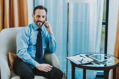 Waist up of cheerful businessman talking on the phone in hotel room stock image