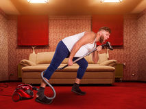 Adult man sings to the vacuum cleaner Royalty Free Stock Photo