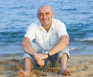 Adult man sitting on   beach Stock Image
