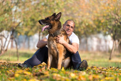 Adult Man Sitting Outdoors With His German Shepherd Stock Photo