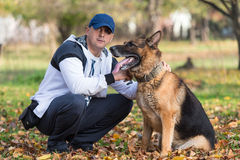 Adult Man Sitting Outdoors With His German Shepherd Royalty Free Stock Photo