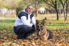Adult Man Sitting Outdoors With His German Shepherd Stock Images