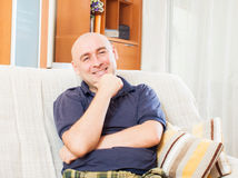 Adult man sitting on sofa royalty free stock photo