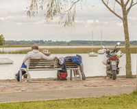 Adult Man Sitting Watching the River. MONTEVIDEO, URUGUAY, MAY - 2015 - Back view of adult baldhead man sitting watching the river at the boardwalk in the coast Royalty Free Stock Images