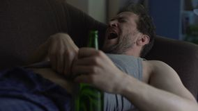 Adult man sleeping on couch holding beer bottle, yawning and scratching belly. Stock footage stock footage